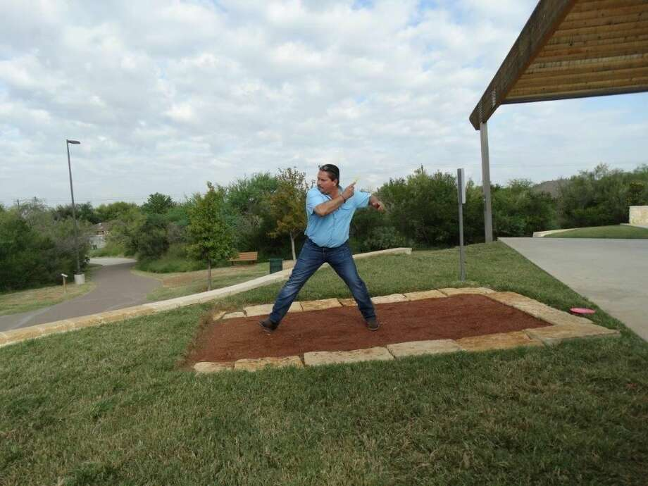 Laredo City Councilman Charlie San Miguel tosses a Frisbee Wednesday during the inauguration of the Frisbee golf course at North Central Park. READ MORE: http://bit.ly/1wH97Gl (Courtesy photo)