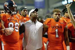 UTSA Roadrunners head coach Frank Wilson (center) stands with players  Baylen Baker (99), left,  Devron Davis (1), and others during the school song after the game with UTEP Saturday Oct. 22, 2016 at the Alamodome. UTEP won 52-49 in quintuple-overtime.