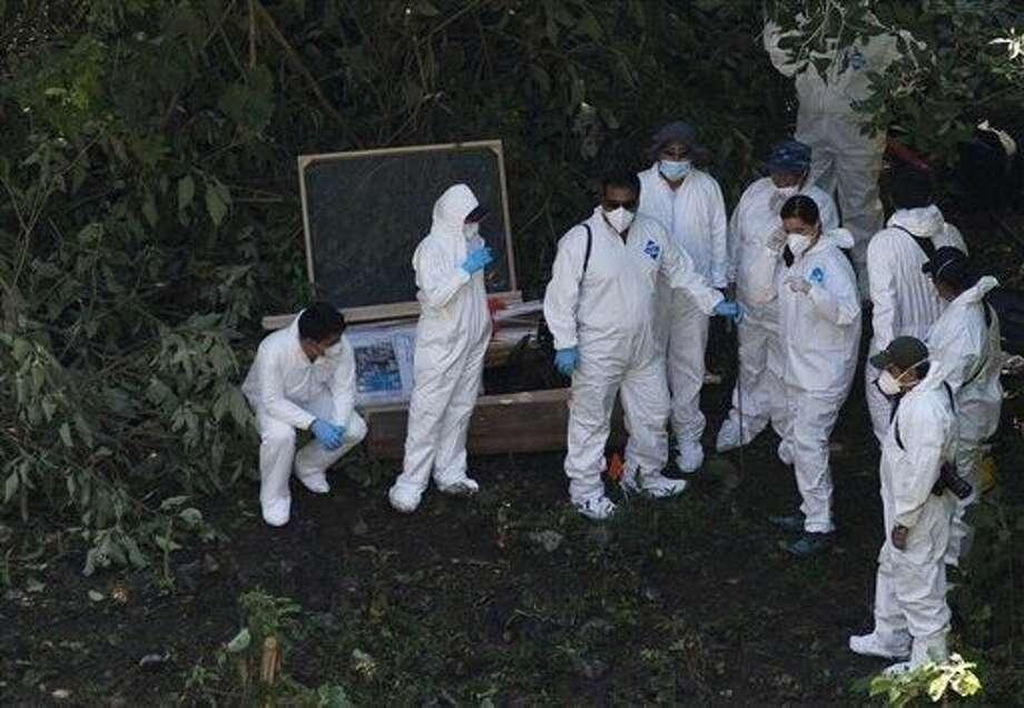 Empleados forenses trabajan en la inspección de restos humanos, por debajo de una ladera llena de basura, en las montañas boscosas cerca de Cocula, en el estado mexicano de Guerrero, el martes 28 de octubre de 2014. Los sospechosos arrestados esta semana dijeron a los fiscales que muchos de los 43 estudiantes que desaparecieron el 26 de septiembre en la ciudad de Iguala fueron retenidos cerca de este lugar. (Foto por Rebecca Blackwell
