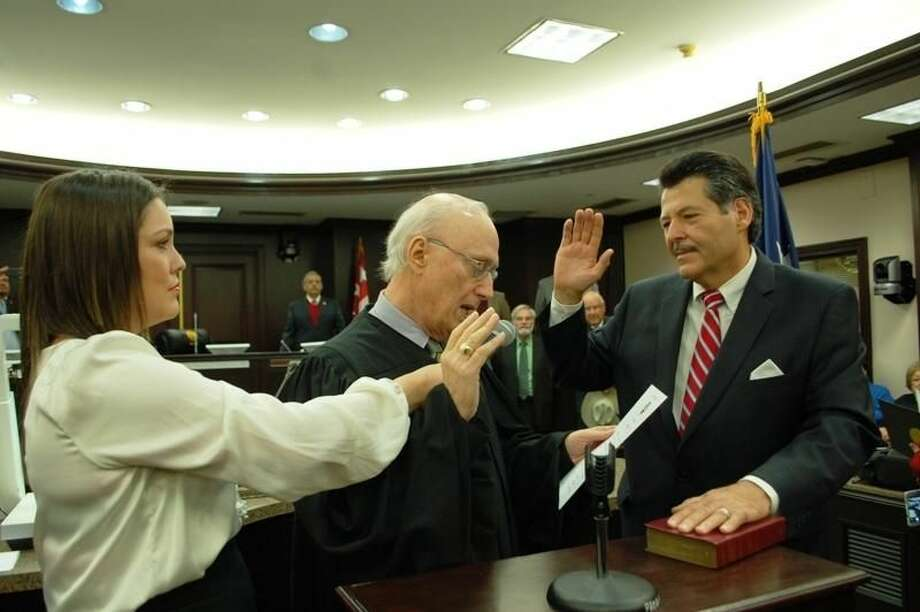 The new Laredo mayor, Pete Saenz, right, takes the oath of office Wednesday at City Hall Council Chambers. U.S. District Judge George Kazen administered the oath of office. Saenz's daughter, Monica Saenz-Vigil, holds the microphone. READ MORE: http://bit.ly/1Ev9xAu (Courtesy photo/City of Laredo)