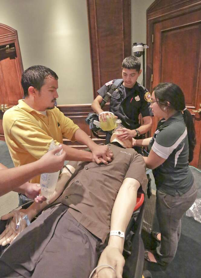 Laredo Fire Department paramedic Christian De Los Santos, center, is joined by LCC Vocational Nursing Program students, Marcos Del Bosque and Frances Sanchez, as they attempt to save a Smart Hospital manikin's life during a simulated cardiac arrest rescue demonstration Wednesday afternoon at the UT Health Science Center Regional Campus-Laredo. (Photo by Victor Strife/Laredo Morning Times)