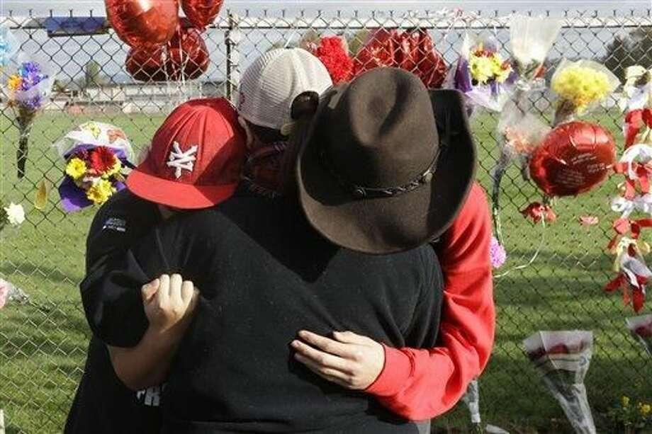 Elijah McGourty, de 15 años, derecha, y su esposa Kylah, de 16, izquierda, abrazan a su madre Mary McGourty, al centro, el lunes 27 de octubre de 2014 junto a un monumento conmemorativo sobre una cerca alrededor de la escuela secundaria Marysville Pilchuck en Marysville, Washington. El viernes 24 de octubre de 2014, el alumno Jaylen R. Fryberg abrió fuego en la cafetería, con lo que mató a dos estudiantes, hirió a tres y luego se suicidó. Otro alumno murió posteriormente. (Foto por Ted S. Warren