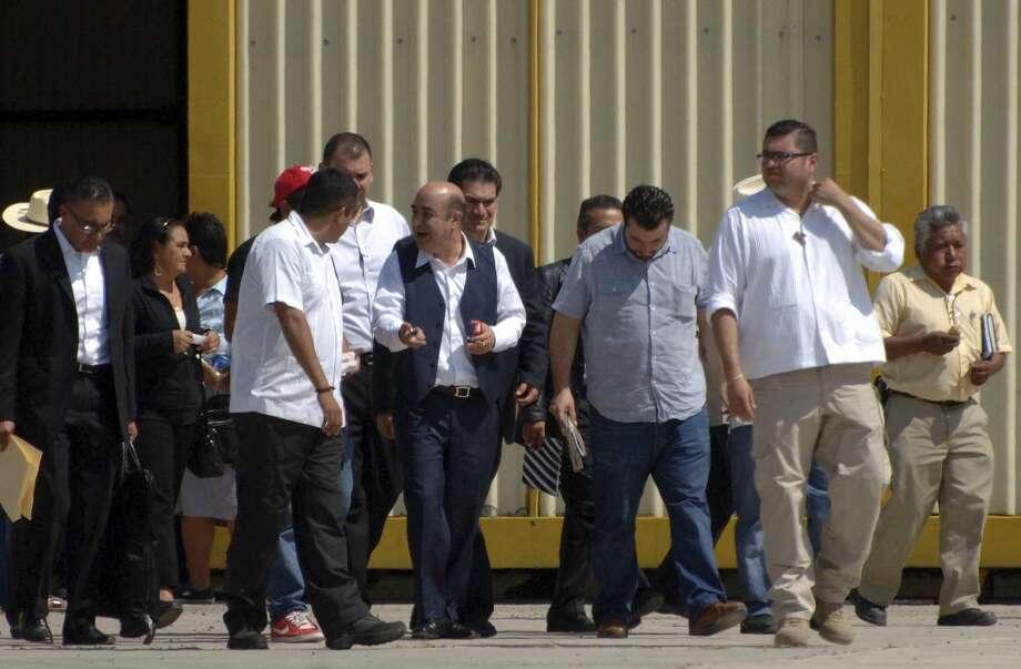 El procurador general de México, Jesús Murillo Karam (al centro a la izquierda), vestido con chaleco azul, sale de un hangar de la ciudad de Chilpancingo, México, después de reunirse el viernes con familiares de 43 estudiantes desaparecidos. (Foto Alejandrino González/AP)