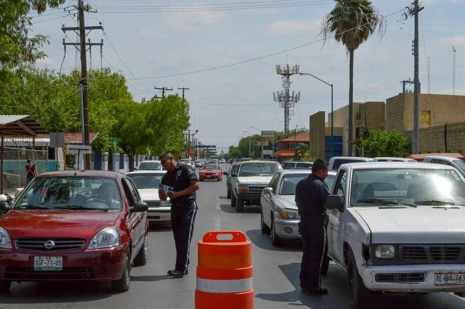 Elementos de tránsito de Nuevo Laredo, México, entregan información a automovilistas orientándolos acerca de la importancia de evitar enviar mensajes de texto mientras se conduce. (Foto de cortesía)