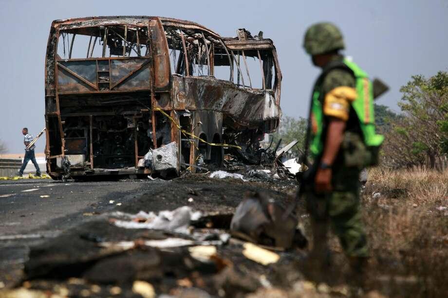 Un soldado custodia el sitio en el que quedó un autobús de pasajeros que se incendió tras chocar con un camión cerca de Ciudad Isla en el estado de Veracruz, México, el domingo. (AP foto/Felix Marquez)