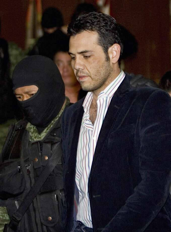 In this March 19, 2009 file photo, military officers escort alleged drug trafficker Jesus Vicente Zambada Niebla during his presentation to the media in Mexico City. Documents unsealed Thursday, April 10, 2014, by the U.S. Attorney's Office in Chicago show Zambada, a high-ranking member of the Sinaloa cartel in Mexico, pleaded guilty to drug trafficking in April 2013 and has been cooperating with authorities. (AP Photo/Eduardo Verdugo, File)