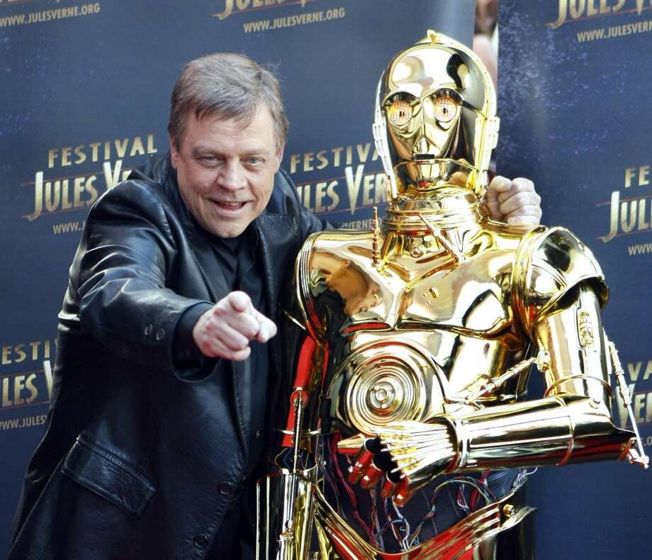 "FILE - In this April 23, 2010 file photo, American actor Mark Hamill who played Luke Skywalker in the George Lucas Star Wars saga poses with a figure of the movie, C 3 PO, before the screening of ""Star Wars V-The Empire Strikes Back,"" as part of the Jules Verne Festival in Paris. After months of carefully guarded secrecy and endless Internet speculation, the cast of the latest incarnation of the space epic, ""Star Wars: Episode VII,"" was unveiled Tuesday, April 29, 2014, on the official ""Star Wars"" website by Lucasfilm and the Walt Disney Co. The ""Episode VII"" cast is a mix of fresh faces, up-and-comers and established names, including veterans Harrison Ford, Hamill and Carrie Fisher. (Photo/Remy de la Mauviniere, file)"