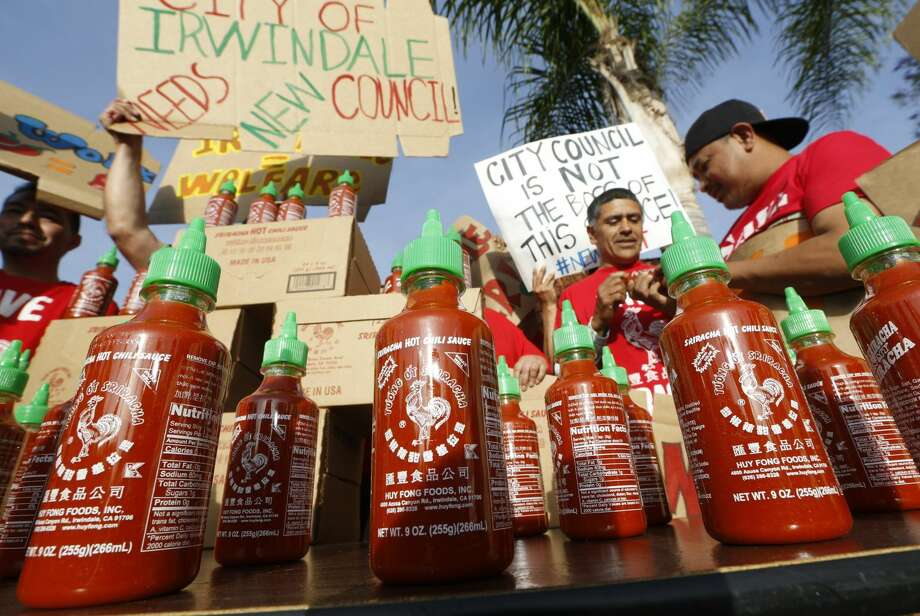 Sriracha hot sauce bottles are set by supporters protesting ahead of the city council meeting in Irwindale, Calif., Wednesday, April 23, 2014. The Irwindale City Council has declared that the factory that produces the popular Sriracha hot sauce is a public nuisance. (AP Photo/Damian Dovarganes)