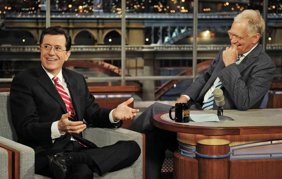 "In this May 3, 2012 photo provided by CBS, Stephen Colbert, left, host of the ""Colbert Report"" on the Comedy Central Network, has a laugh on stage with host David Letterman on the set of the ""Late Show with David Letterman,"" in New York. CBS announced on Thursday, April 10, 2014 that Colbert will replace Letterman as ""Late Show"" host after Letterman retires in 2015. (AP Photo/CBS, John Paul Filo)"