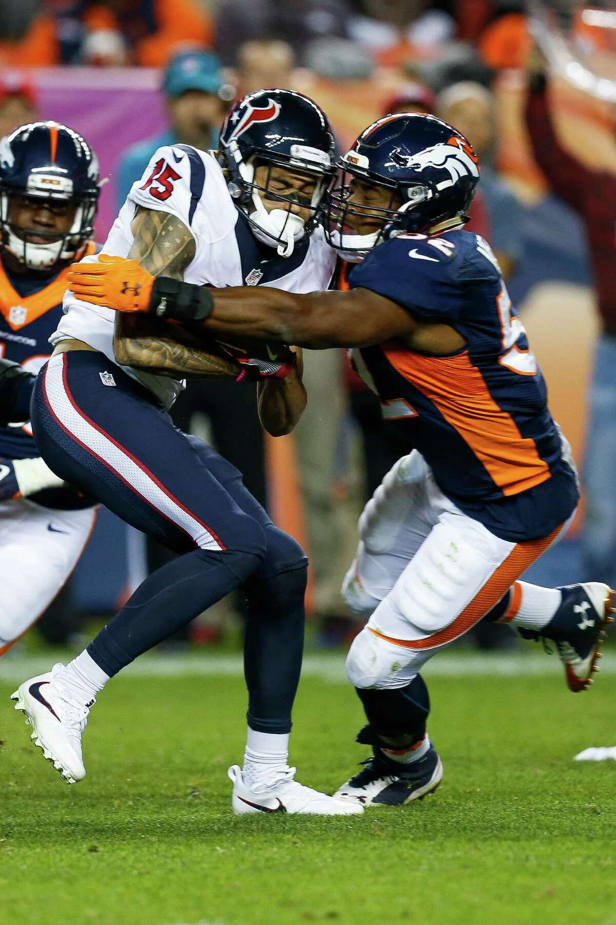 Houston Texans wide receiver Will Fuller (15) takes a hit from Denver Broncos outside linebacker Corey Nelson (52) during the fourth quarter of an NFL football game at Sports Authority Field at Mile High on Monday, Oct. 24, 2016, in Denver.