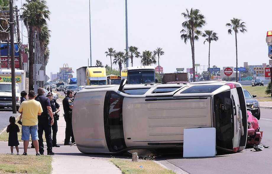 The driver and passengers stand near their vehicle as Laredo police and fire department officers investigate the scene of a of a two-vehicle rollover accident at the 5600 block of San Dario Avenue and I-35's Mann Road pn Friday afternoon. (Cuate Santos/Laredo Morning Times)