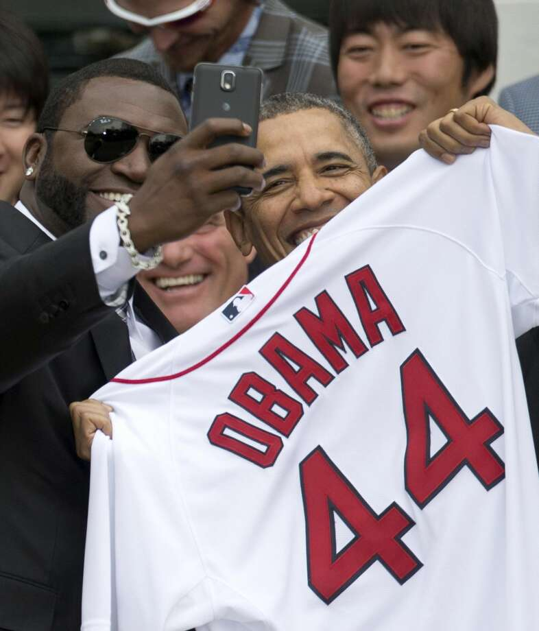 """FILE - In this Tuesday, April 1, 2014, file photo, Boston Red Sox designated hitter David """"Big Papi"""" Ortiz takes a selfie with President Barack Obama, holding a Boston Red Sox jersey presented to him, during a ceremony on the South Lawn of the White House in Washington, where the president honored the 2013 World Series baseball champion Boston Red Sox. Ortiz tweeted the selfie to his followers Tuesday, and it was resent by tens of thousands, including Samsung, which retweeted it as an ad. The White House press secretary says Obama was not aware that the photo was part of a marketing stunt. (AP Photo/Carolyn Kaster, File)"""