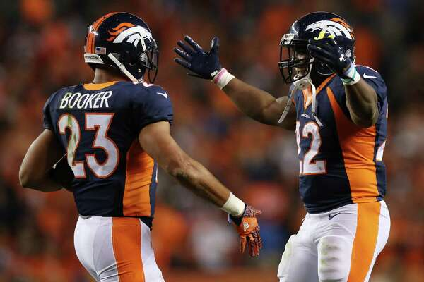 DENVER, CO - OCTOBER 24:  Running back Devontae Booker #23 and running back C.J. Anderson #22 of the Denver Broncos celebrate a score in the second half of the game against the Houston Texans at Sports Authority Field at Mile High on October 24, 2016 in Denver, Colorado.