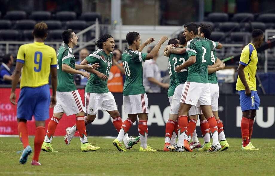 Fidel Martínez (9) y Jaime Ayovi (17) de Ecuador, se quedan varados, mientras jugadores de México celebran un gol realizado por Luis Montes en la primera mitad del encuentro de fútbol soccer amistoso, el sábado, en Arlington. (Foto por Tony Gutierrez/AP)