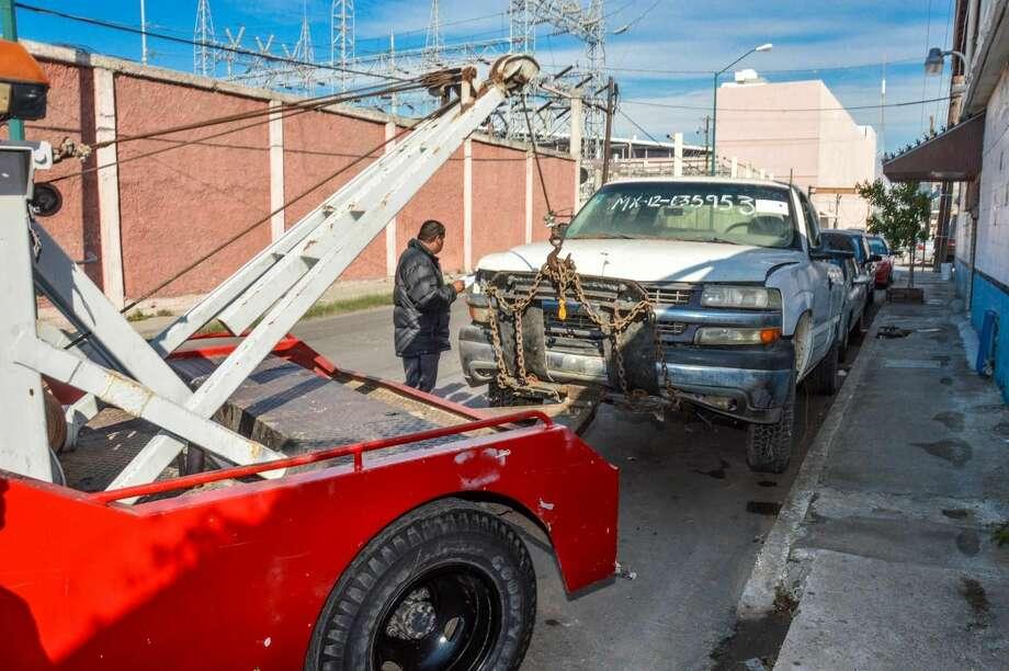 Oficiales de tránsito retiran una camioneta abandonada en la vía pública, en el marco de la campaña 'Mueve tu Chatarra'. (Foto de cortesía)