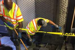 BART crews clean gunk under escalator grate at Powell Street station (Brandon M. Mercer / SFGATE)