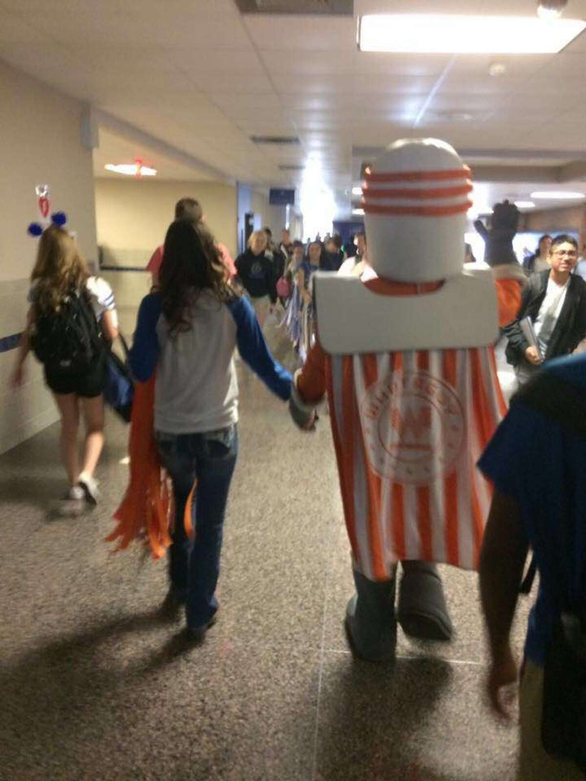Friendswood freshman Gracie Kempken walks away with Whataguy, her homecoming date, after the Whataburger mascot accepted her invitation via tweet.