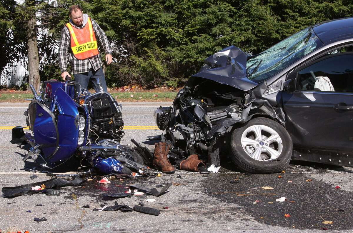 LITCHFIELD, CT - 23 October 2016 - 102316JM03 - A Litchfield, Conn. emergency services volunteer checks out the car and one of several motorcycles that were involved in an accident of Route 63 in Litchfield, Conn. on Sunday, October 23rd 2016. (AP Photo/The Republican-American, John McKenna)