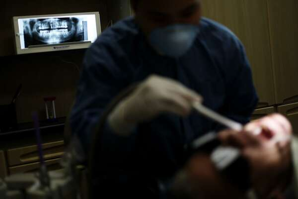 A dental X-ray for a patient rests against a light table while he has suction applied by volunteer dental assistant at San Antonio Christian Dental Clinic on the Haven for Hope campus in 2009.