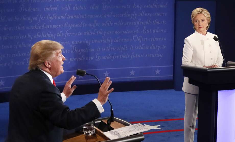 Republican nominee Donald Trump gestures as Democratic nominee Hillary Clinton looks on during the final presidential debate at the Thomas & Mack Center on the campus of the University of Las Vegas in Las Vegas, Nevada on October 19, 2016.