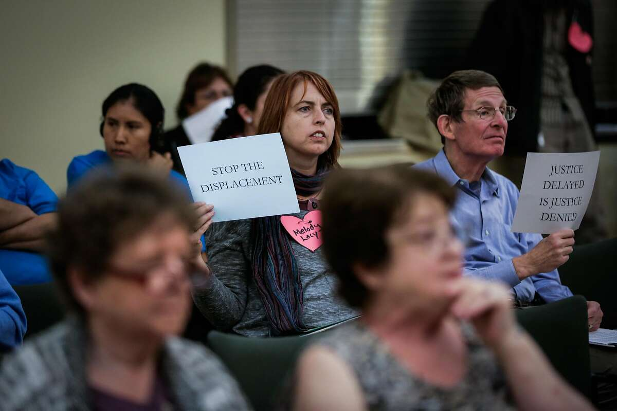 Activist Kristi Laughlin (left) and Bob Lane (right), hold up signs in favor of a housing moratorium, during the Concord City Council's Housing and Economic Development Committee meeting, in Concord, California, on Monday, Oct. 24, 2016.