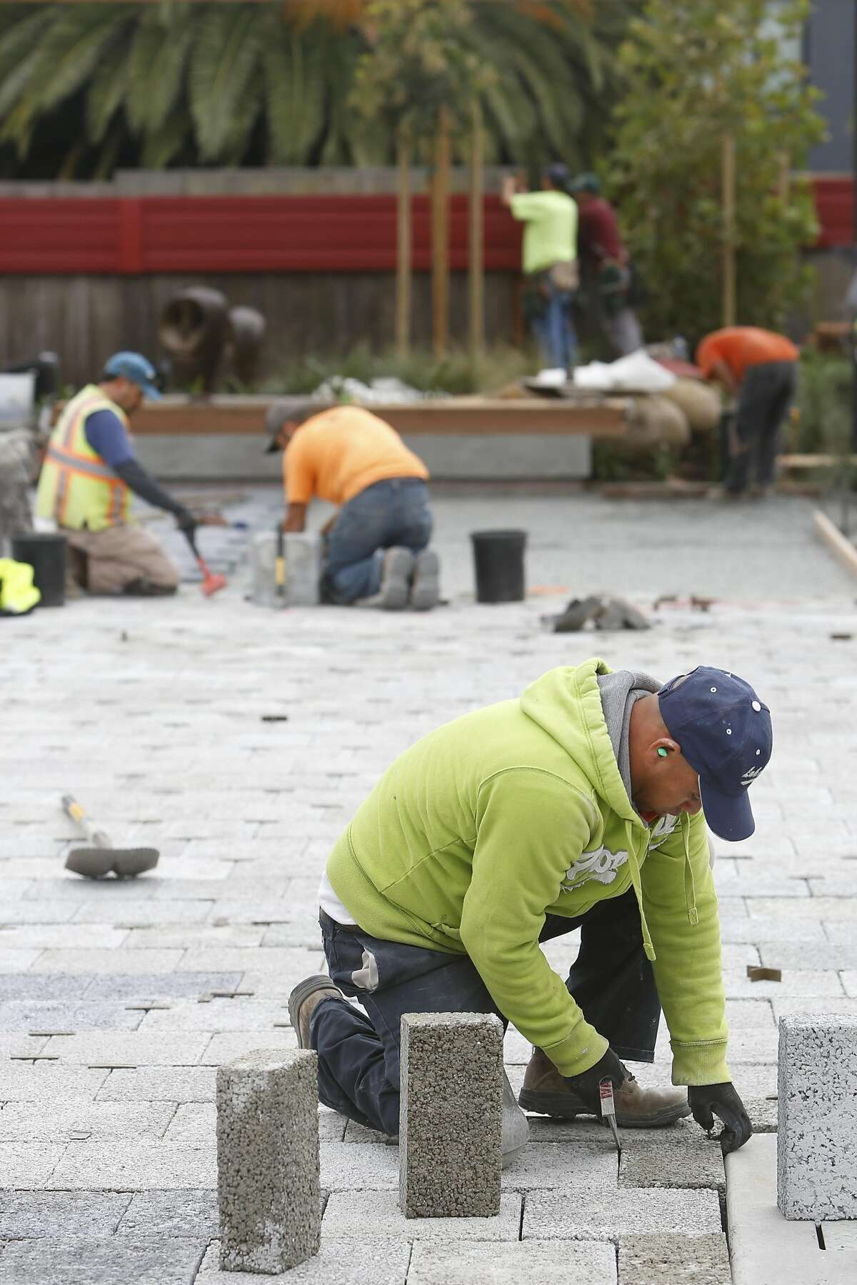 Edgar Guerrero, laborer Bauman Landscape and Construction, screeds rocks for pavers at Noe Valley Town Square on Monday, October 24, 2016 in San Francisco, Calif.