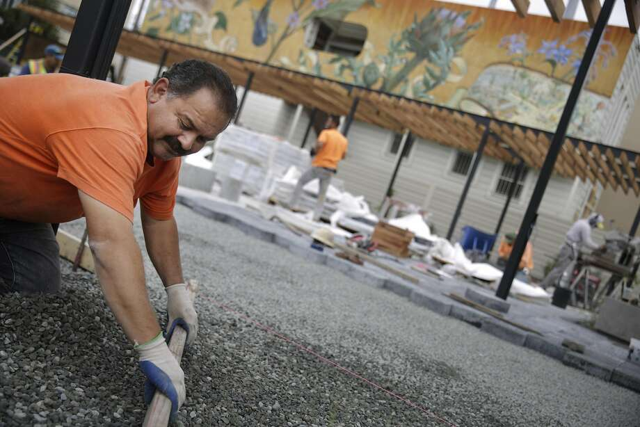 Fidel Vargas works on installing pavers in the Noe Valley town square just before its opening day. Photo: Lea Suzuki, The Chronicle