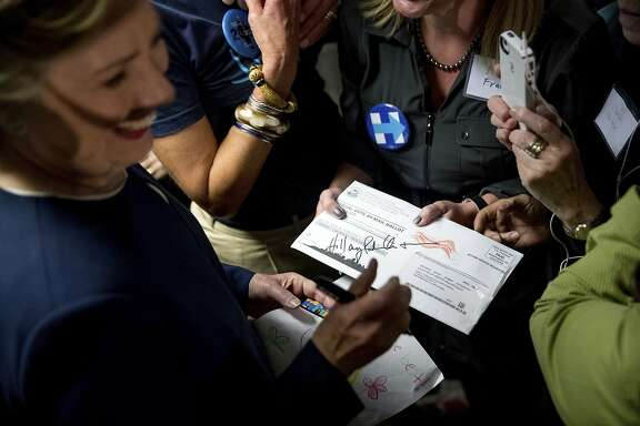 Democratic presidential candidate Hillary Clinton signs a vote-by-mail ballot letter as she greets volunteers at a campaign field office in San Francisco, Thursday, Oct. 13, 2016. (AP Photo/Andrew Harnik)