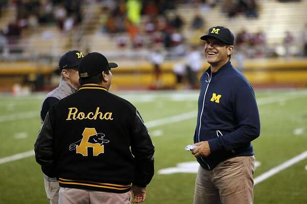 Michigan's head coach of football Jim Harbaugh, (right) who was there to watch star running back Najee Harris play, along with school principal Louie Rocha before the start of the game, as the Antioch Panthers take on the Liberty Lions in high school football action in Antioch, California, on Friday October 14, 2016