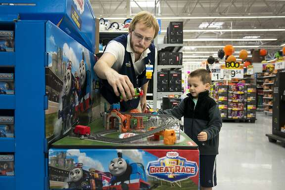 -- PHOTO MOVED IN ADVANCE AND NOT FOR USE - ONLINE OR IN PRINT - BEFORE OCT. 16, 2016. -- Bobby Davis, a Walmart associate, prepares a ÒThomas and FriendsÓ display, while a boy plays with the train set, in Fayetteville, Ark., Oct. 12, 2016. After WalmartÕs revenue fell in 2015 for the first time in its 45-year run as a public company, the company was forced to reorganize, starting with increasing wages for its workers. (Melissa Lukenbaugh/The New York Times)