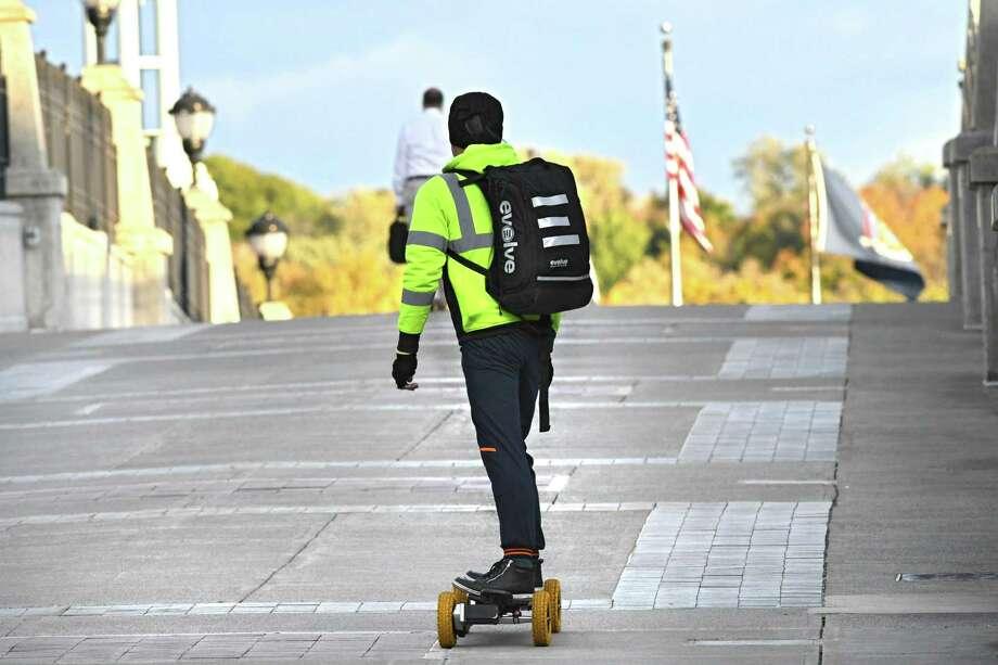 A man riding a motorized longboard makes his way over the pedestrian bridge towards Jenning's Landing  on Monday, Oct. 24, 2016 in Albany, N.Y.  (Lori Van Buren / Times Union) Photo: Lori Van Buren