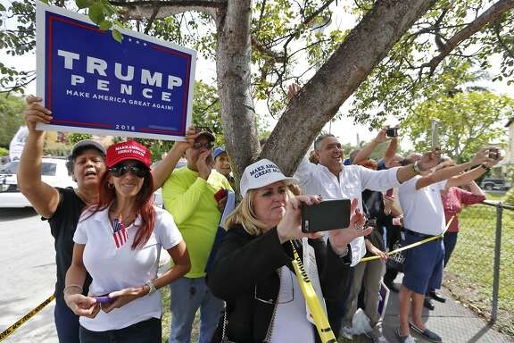 Trump supporters wave to Donald Trump after the presidential nominee leaves the Bay of Pigs museum after addressing the Brigade 2506, veterans of the Cuban battle on Tuesday, October 25, 2016. (Al Diaz/Miami Herald via AP)