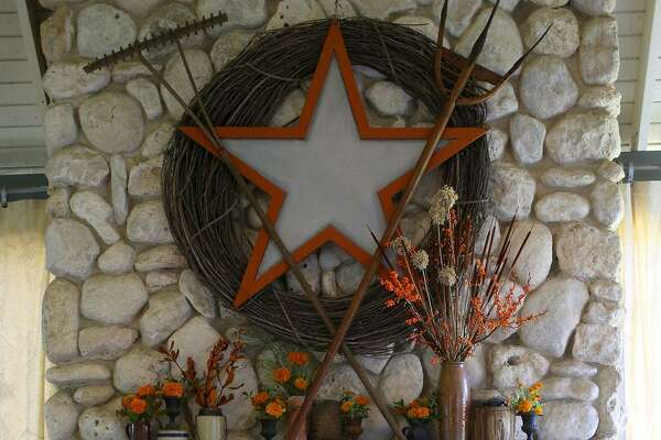"Take one element in your home and make it a focal point for your ""naturescape."" With a glowing fire inviting family to gather 'round, the mantle can become the center of attention.  Here, a giant grapevine wreath centered with a galvanized metal sign in the shape of a Texas star is surrounded by antique farm implements used for harvesting crops. An assortment of crockery jars, pitchers and small wrought-iron urns are filled with picked orange marigolds. Dried garlic pods, possum haw holly branches, dried leaves and cattails."