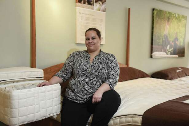 Store manager Courtney Zwerver poses with a selection of organic mattresses at the Naturepedic mattress showroom in Greenwich, Conn. Tuesday, Oct. 25, 2016. Naturepedic is an organic mattress company based in Ohio and just opened a gallery at 79 E. Putnam Ave. in Greenwich and will have an official ribbon-cutting on Nov. 4.
