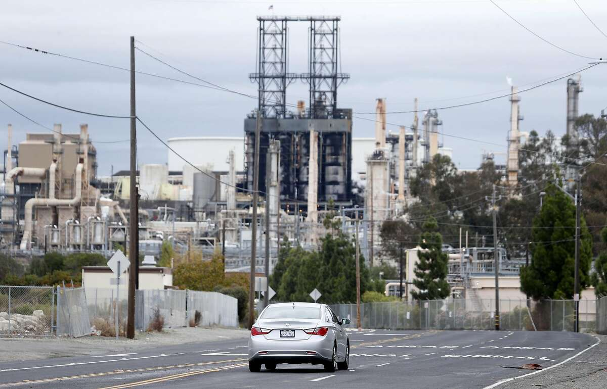 A car drives on San Pablo Avenue towards the Phillips 66 refinery, which borders the Bayo Vista neighborhood in Rodeo, Calif. on Tuesday, Oct. 25, 2016.