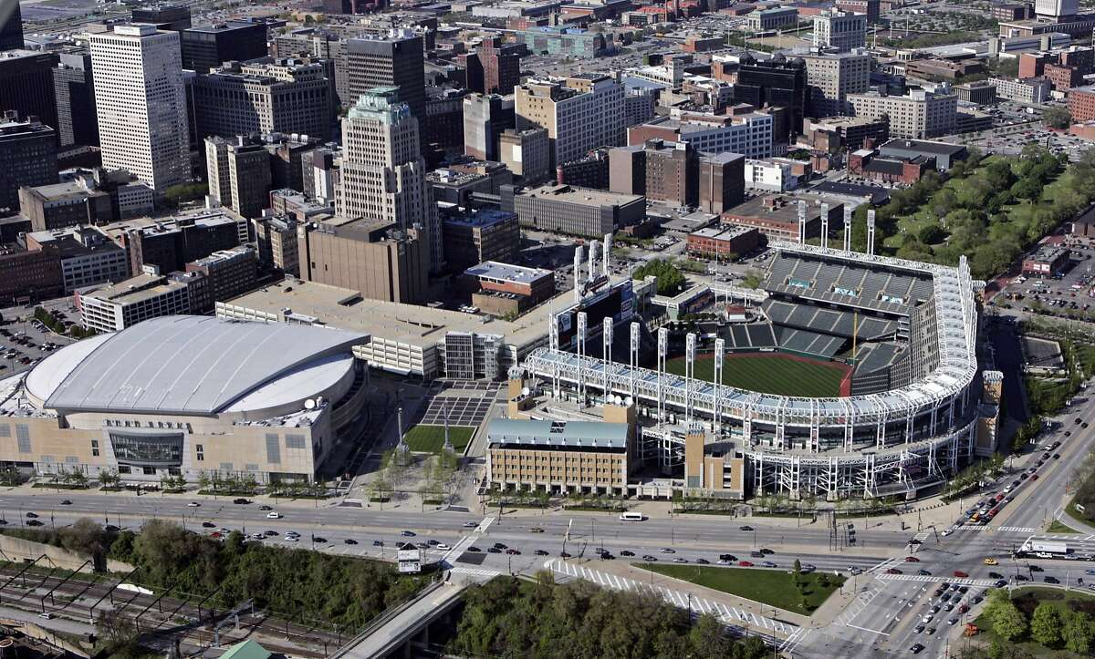 FILE - This May 20, 2005, file photo shows Jacobs Field (now Progressive Field), right, and Gund Arena (now Quicken Loans Arena) in Cleveland. When LeBron James and the Cavaliers, whose historic comeback in June against Golden State in the NBA Finals ended Cleveland�s title drought dating to 1964, receive their championship rings and a banner is raised in Quicken Loans Arena before their season opener, the emotional ceremony will merely be the warm-up act. Next door, at Progressive Field, the Indians will host the Chicago Cubs in Game 1 of the World Series. (AP Photo/Mark Duncan, File)