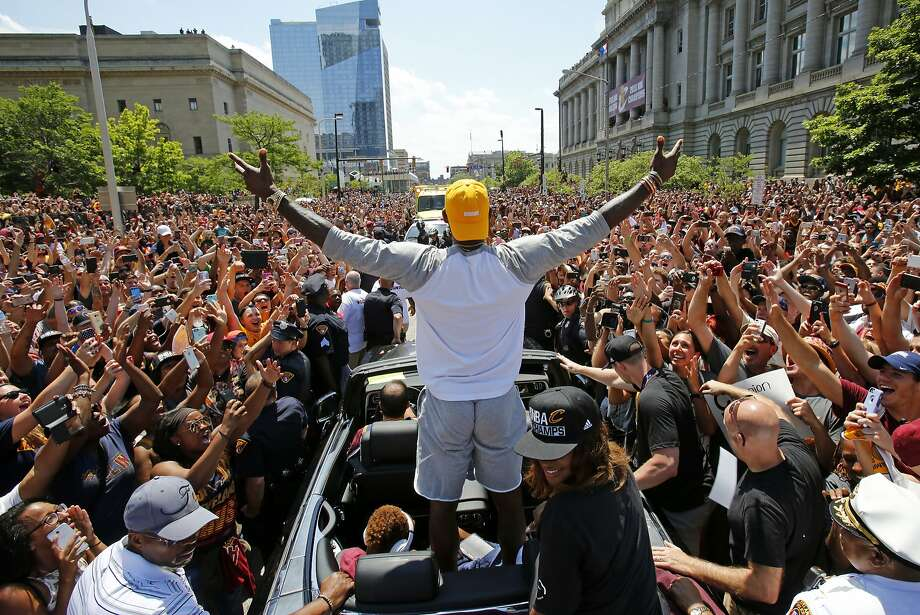 FILE - In this June 22, 2016, file photo, Cleveland Cavaliers' LeBron James, center, stands in the back of a Rolls Royce as it makes its way through the crowd lining the parade route in downtown Cleveland, celebrating the basketball team's NBA championship. When LeBron James and the Cavaliers, whose historic comeback in June against Golden State in the NBA Finals ended Cleveland's title drought dating to 1964, receive their championship rings and a banner is raised in Quicken Loans Arena before their season opener, the emotional ceremony will merely be the warm-up act. Next door, at Progressive Field, the Indians will host the Chicago Cubs in Game 1 of the World Series. (AP Photo/Gene J. Puskar, File) Photo: Gene J. Puskar, Associated Press