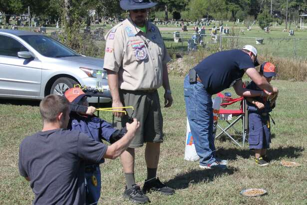 Young Cub Scouts Dylan Burns (left) and Braydn Moya (right)learn how to use slingshots under the supervision of Cub Master Pack 300 Douglas Green (middle). Burns is assisted by his uncle Chris Knepper while Moya is assisted by Douglas Harris.