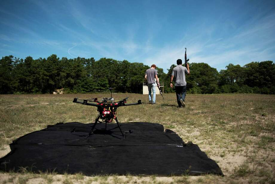 Jacob Regenstein and Ben Krosner with fake rifles for an autonomous drone tracking test at Joint Base Cape Cod, Mass., Aug. 25, 2016. The U.S. has put artificial intelligence at the center of its defense strategy, with weapons that can identify targets and make decisions. (Hilary Swift/The New York Times) Photo: HILARY SWIFT, NYT / NYTNS