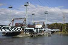 A southbound Metro-North train passes across the railroad bridge spanning Cos Cob Harbor in the Cos Cob section of Greenwich. The 1904 movable bridge did not close properly after it opened to allow river traffic to pass Tuesday morning, causing delays for commuters aboard the New Haven line trains.