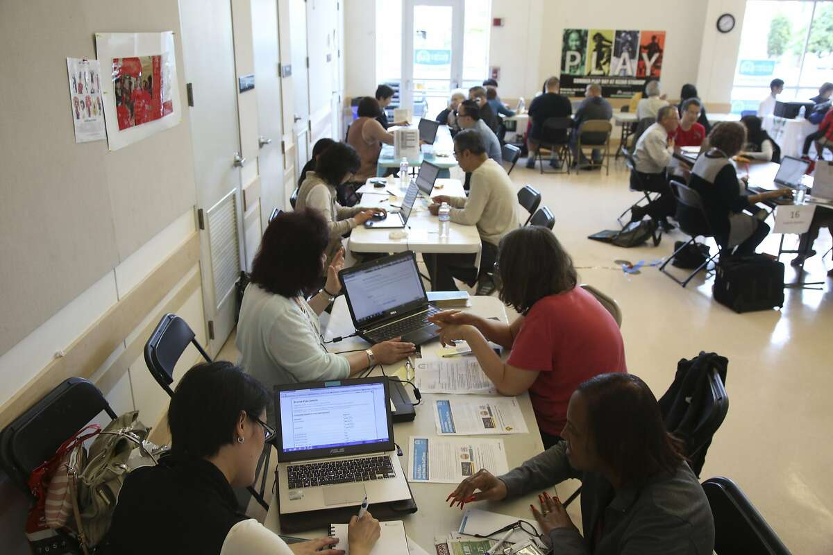 FILE -- A health insurance fair on the first day of open enrollment for the Affordable Care Act at the the Richmond Recreation Center in San Francisco, Nov. 1, 2015. Market shifts and exits of large insurers are leaving Obamacare customers with no-frills plans that limit their choices of doctors and hospitals. (Jim Wilson/The New York Times)