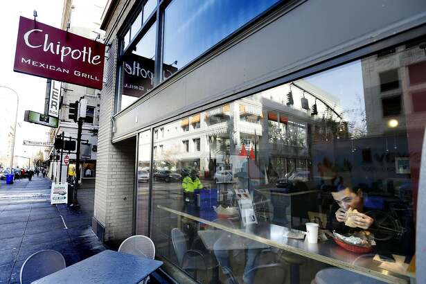 FILE - In this Wednesday, Nov. 11, 2015, file photo, a customer enjoys lunch at a Chipotle restaurant in Portland, Ore. Chipotle reports financial results Tuesday, Oct. 25, 2016. (AP Photo/Don Ryan, File)