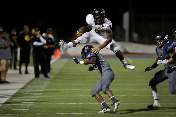 Antioch High School star running back Najee Harris vaults over Falcon defender Jared Rodgers, 22  as the Panthers take on Freedom High School on Fri. Oct 7, 2016, in Oakley, California.