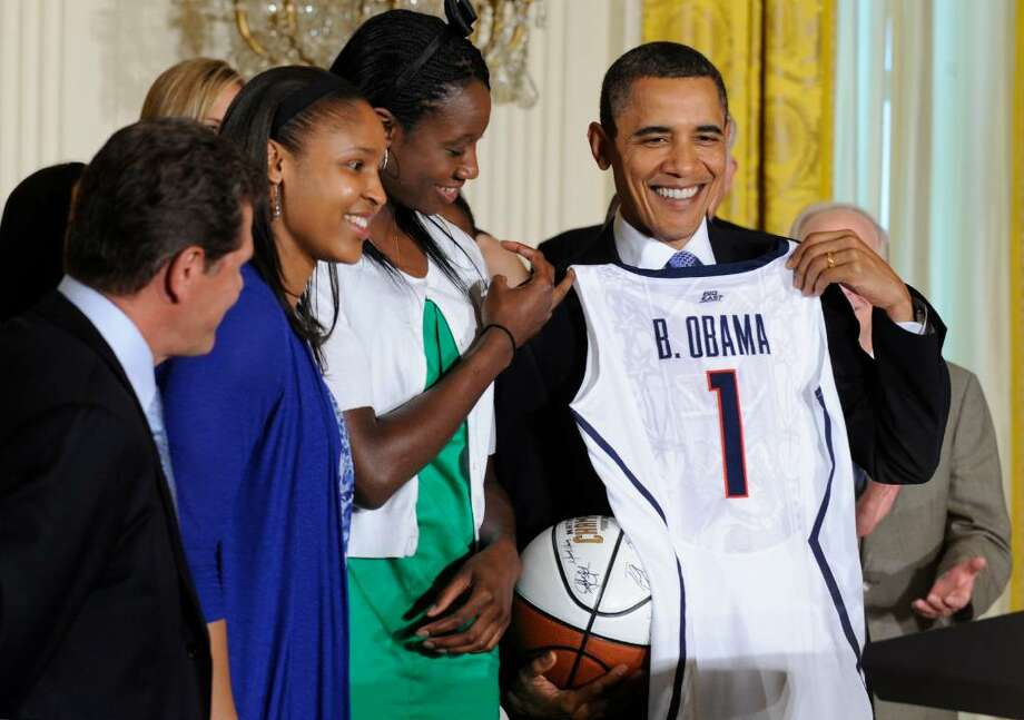 President Barack Obama holds a jersey and basketball that was presented to him by NCAA champion University of Connecticut women's basketball players Tina Charles, in green, and Maya Moore, blue, during a ceremony in the East Room of the White House in Washington, Monday, May 17, 2010. UConn coach Geno Auriemma watches at left. (AP Photo/Susan Walsh) Photo: Susan Walsh, AP / AP