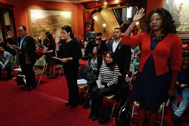U.S. Citizenship and Immigration Services presents 20 candidates for naturalization to the U.S. District Court for the District of Connecticut, including Heather Brown, of Jamaica, right, on Tuesday at Lockwood-Mathews Mansion Museum in Norwalk, Conn. The Honorable Stefan R. Underhill, United States District Judge, District of Connecticut, administered the Oath of Allegiance to America's newest citizens during the naturalization ceremony.