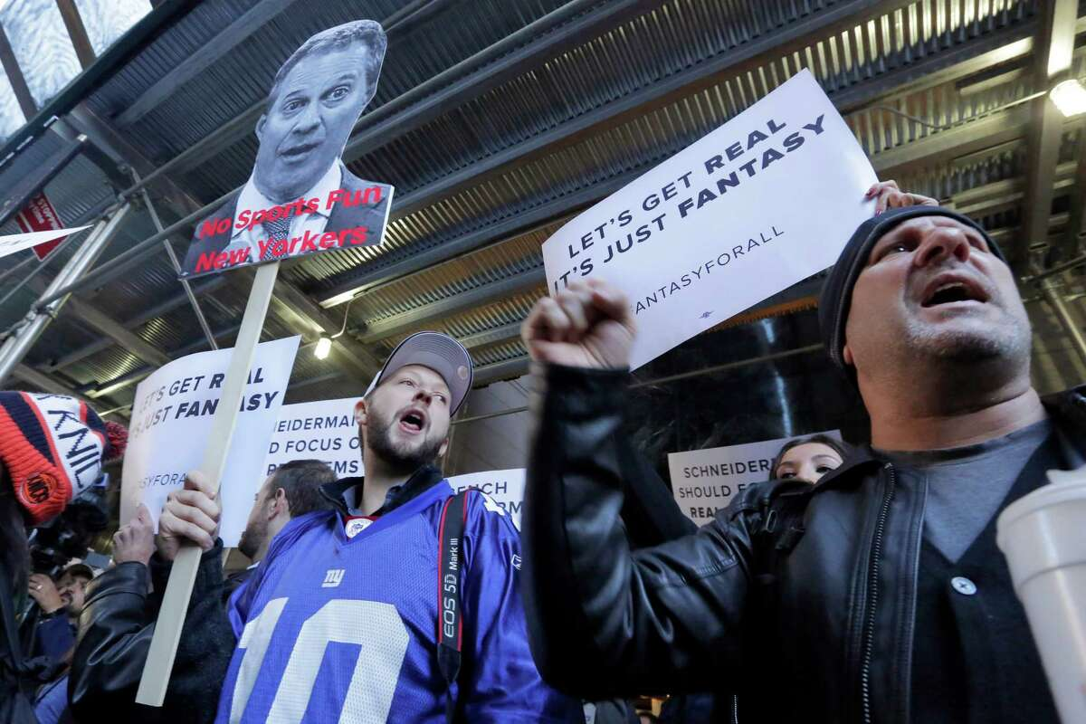 Fantasy sports fans demonstrate outside the Financial District offices of New York state Attorney General Eric Schneiderman, in New York, Friday, Nov. 13, 2015. Schneiderman's decision that daily fantasy sports betting sites FanDuel and DraftKings are illegal gambling operations in his state is a blow to the companies, but the multibillion-dollar industry could have more legal headaches yet to come. (AP Photo/Richard Drew) ORG XMIT: NYRD102