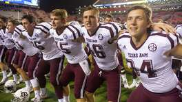 "Texas A&M punter Shane Tripucka (second from left) wings the ""Aggie War Hymn"" with his teammates at Kyle Field in College Station."