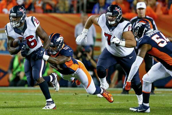 Lamar Miller, left, ran for 61 yards on 11 carries against the Broncos on Monday night despite being limited by a shoulder injury.
