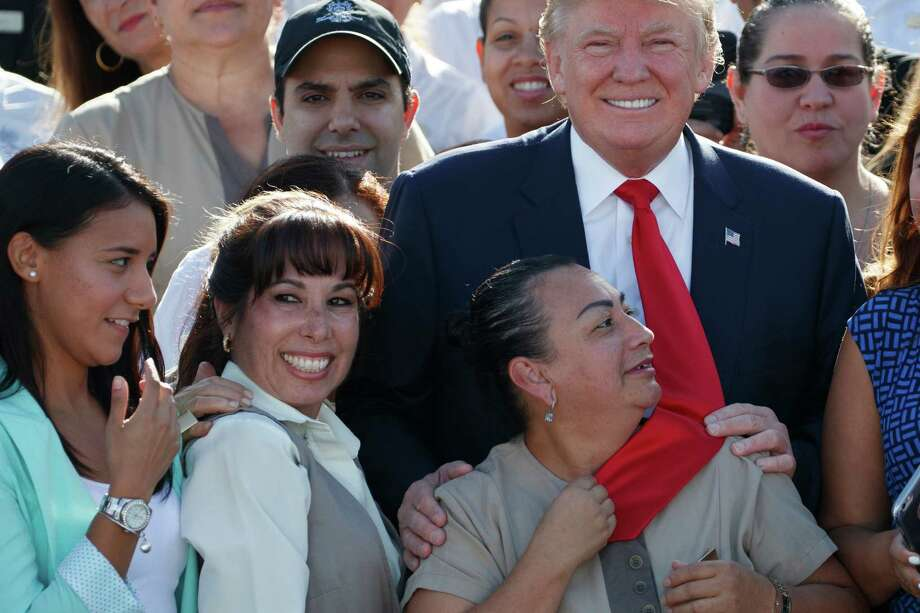 An employee of Republican presidential candidate Donald Trump grabs his tie as they pose for photographs during an event at Trump National Doral, Tuesday, Oct. 25, 2016, in Miami. (AP Photo/ Evan Vucci) ORG XMIT: FLEV111 Photo: Evan Vucci / Copyright 2016 The Associated Press. All rights reserved.