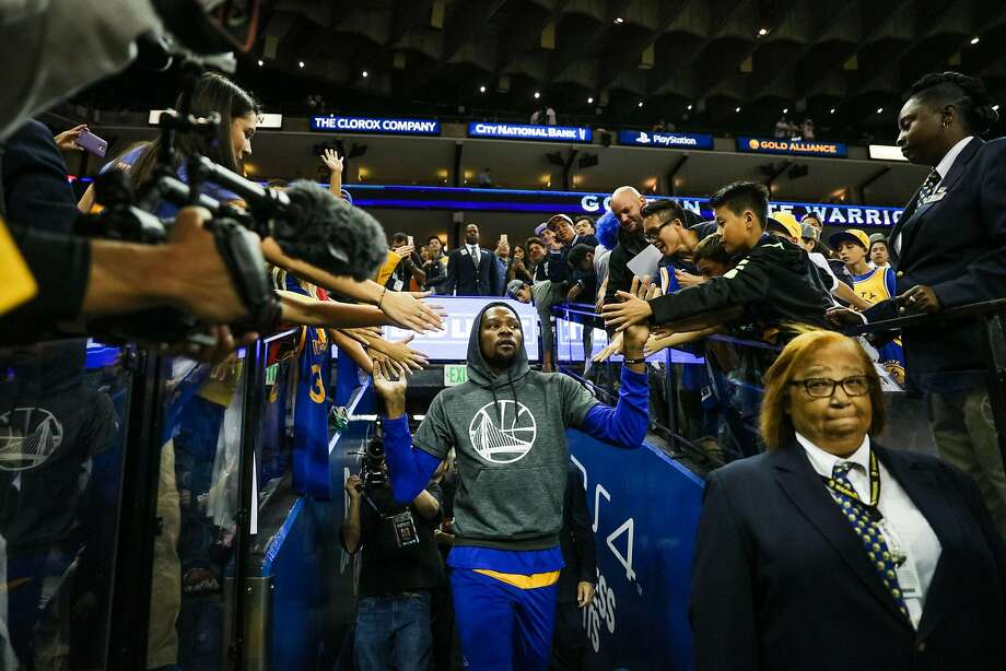 Warriors forward Kevin Durant, #35, gives high fives to fans as he heads to a warm up, ahead of a game between the Warriors vs. the Spurs, at Oracle Arena, in Oakland, California, on Tuesday, Oct. 25, 2016. Photo: Gabrielle Lurie, The Chronicle
